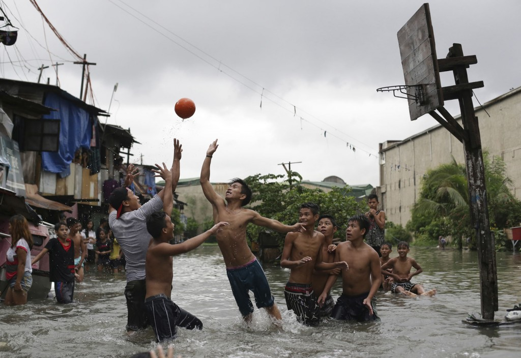 Filipino boys play basketball in floodwaters from a swollen creek at a coastal village in Malabon, north of Manila, Philippines, Wednesday, July 8, 2015. Typhoon Chan-Hom passing over the northeastern waters of the Philippines heading to northern Taiwan has enhanced the seasonal monsoon, dumping heavy rains over the capital, Manila, and the northern provinces. (AP Photo/Aaron Favila)