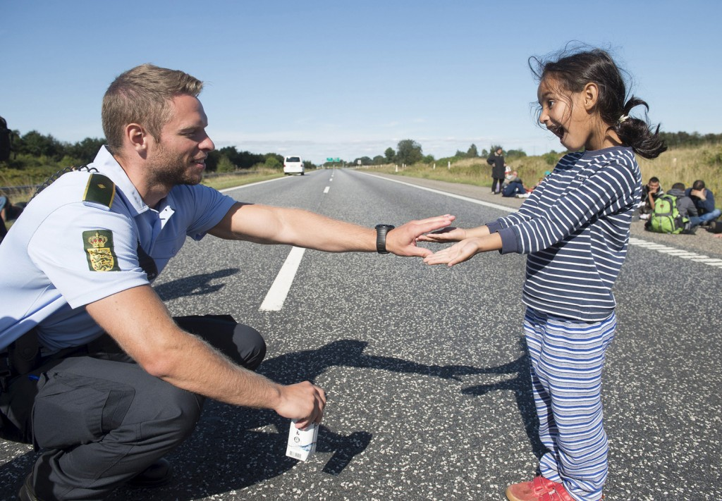A Danish policeman plays with a migrant girl at the E45 freeway north of Padborg September 9, 2015. Many migrants, mainly from Syria and Iraq, have arrived in Denmark over the last few days. The migrants want to reach Sweden to seek asylum there. Some of the migrants arriving in central Europe have continued on to other countries, as local authorities across the continent try to accommodate the rising tide of refugees. The police closed the freeway for security reasons. Picture taken September 9, 2015. REUTERS/Claus Fisker/Scanpix ATTENTION EDITORS - THIS IMAGE WAS PROVIDED BY A THIRD PARTY. FOR EDITORIAL USE ONLY. NOT FOR SALE FOR MARKETING OR ADVERTISING CAMPAIGNS. THIS PICTURE IS DISTRIBUTED EXACTLY AS RECEIVED BY REUTERS, AS A SERVICE TO CLIENTS. DENMARK OUT. NO COMMERCIAL OR EDITORIAL SALES IN DENMARK. NO COMMERCIAL SALES. - RTSNJL
