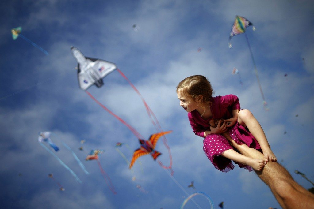 Madeleine Klonoski, 2, sits on her father's leg at a kite festival in Redondo Beach, California March 8, 2015. REUTERS/Lucy Nicholson (UNITED STATES - Tags: SOCIETY TPX IMAGES OF THE DAY) - RTR4SJT4
