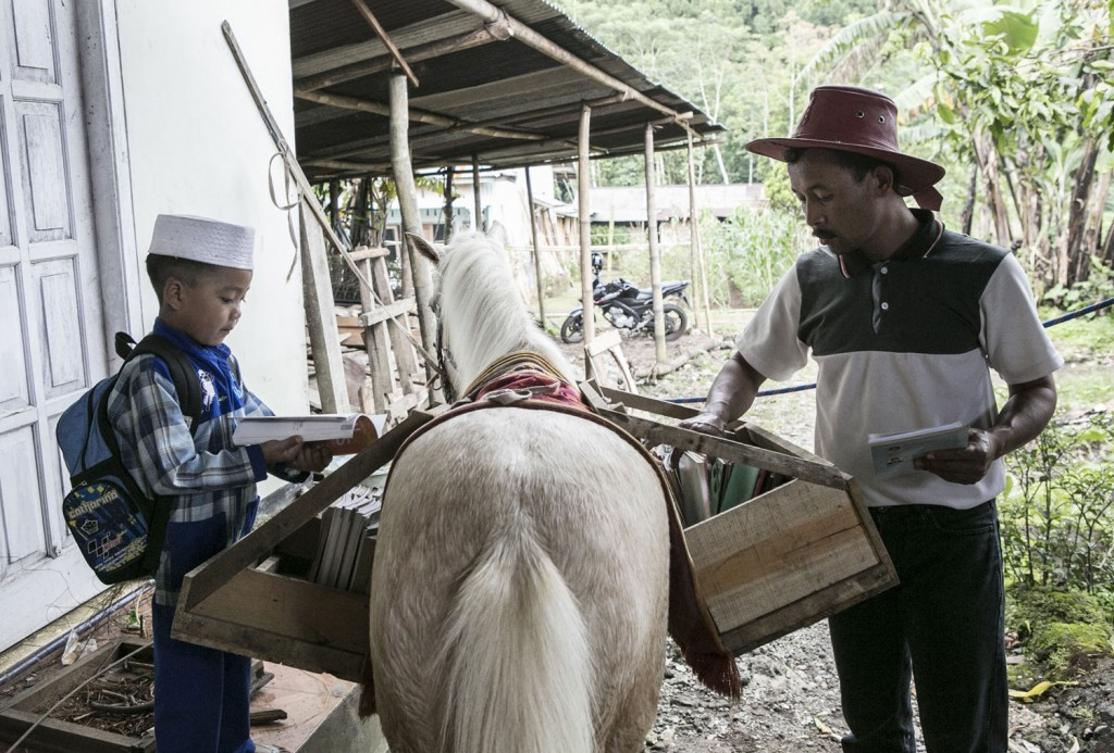 "PURBALINGGA, CENTRAL JAVA, INDONESIA - MAY 05: 42 year old Ridwan Sururi prepares the books while a boy selects book at the mobile library on May 5, 2015 in Serang Village, Purbalingga, Central Java Indonesia. Ridwan, a horses caretaker from Serang Village in Central Java, initiated the mobile library using a horse named ""Kudapustaka"" on January 2015 with book donations from his friend Nirwan Arsuka and other donors. Every week on Tuesday, Wednesday and Thursday he visitÕs nearby schools to offer books for the children. Ê (Photo by Putu Sayoga/Getty Images)"