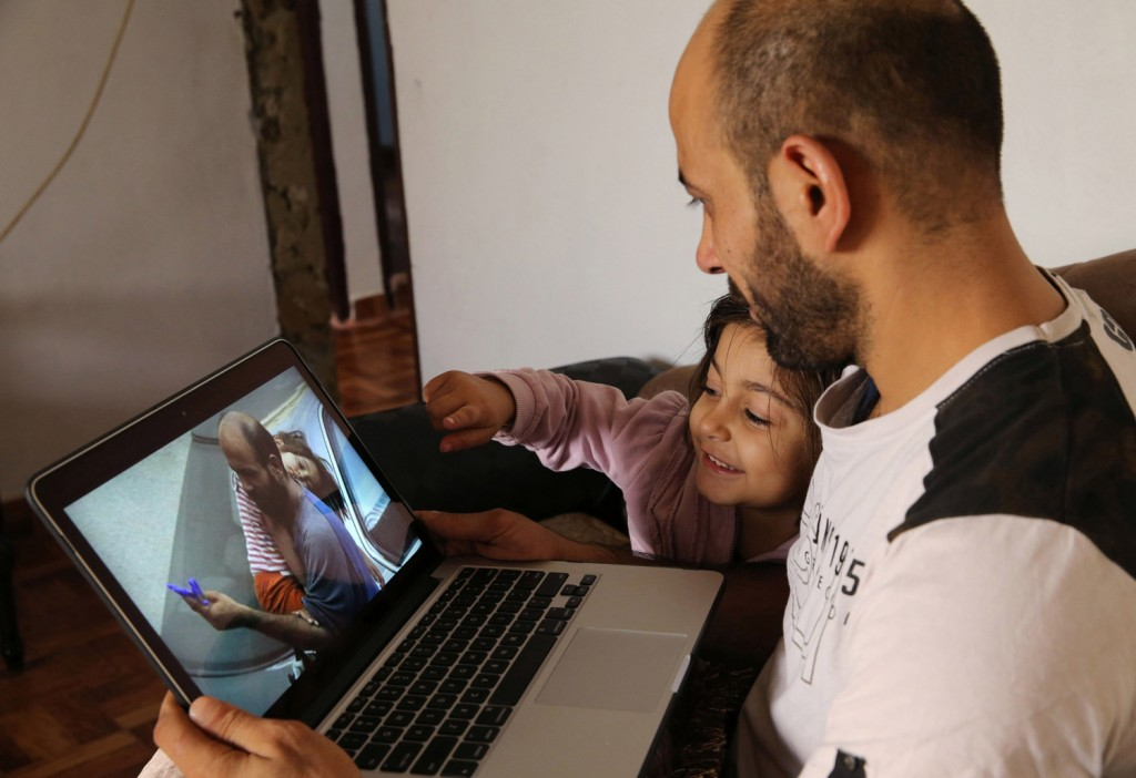 In this picture taken on Saturday, Nov. 28, 2015, Abdul Halim al-Attar, a refugee from Syria sits next his daughter Reem, 4, as they look at a photo on a laptop during an interview with The Associated Press. The photograph of al-Attar carrying his sleeping daughter on his shoulder while trying to sell pens to passing motorists in the scorching heat went viral this past summer and touched people across the world. In this picture taken on Saturday, Nov. 28, 2015, Abdul Halim al-Attar, kisses his daughter Reem, 4, at their house, in Beirut, Lebanon. Al-Attar, a refugee from Syria who was photographed selling pens in the streets of Beirut, is now running three businesses in the city after an online crowdfunding campaign in his name collected $191,000. (AP Photo/Hussein Malla)